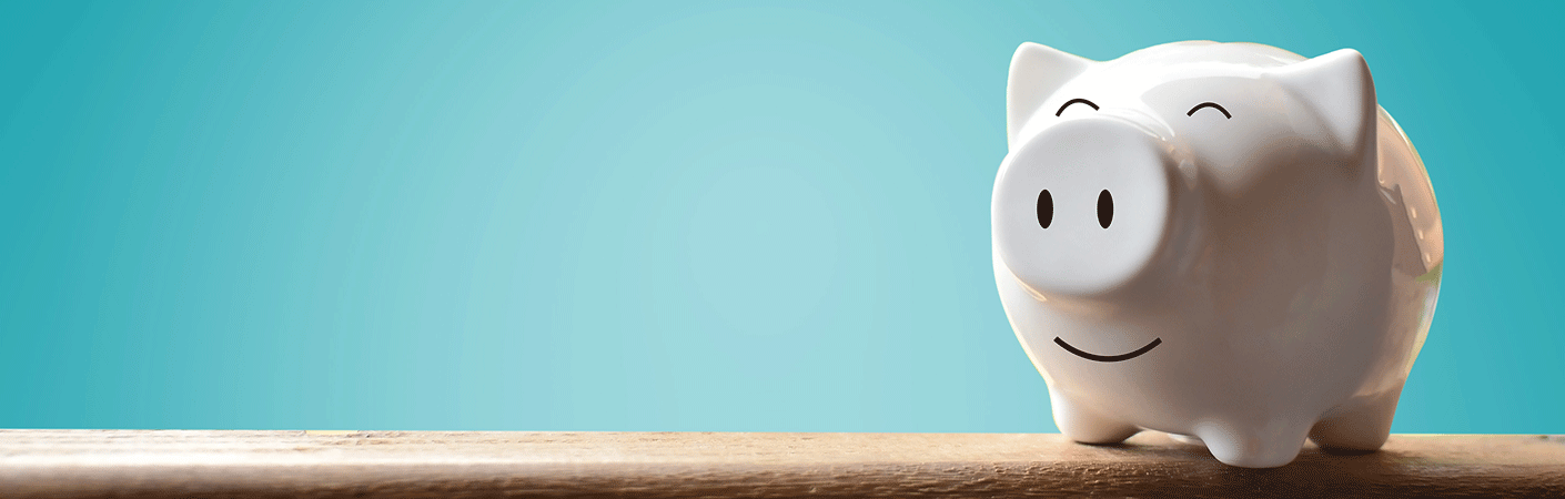 White piggy bank sitting on a piece of wood in front of a light blue background