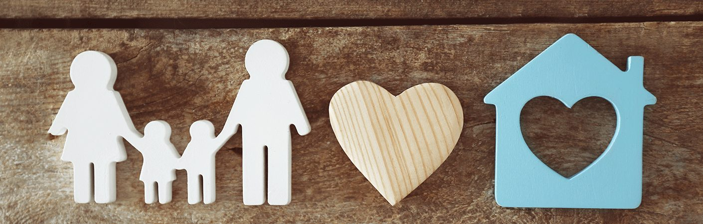 Wooden figures of a family a heart and a house with a heart in the center