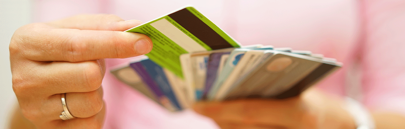 Person holding a variety of credit cards and picking one out of the array
