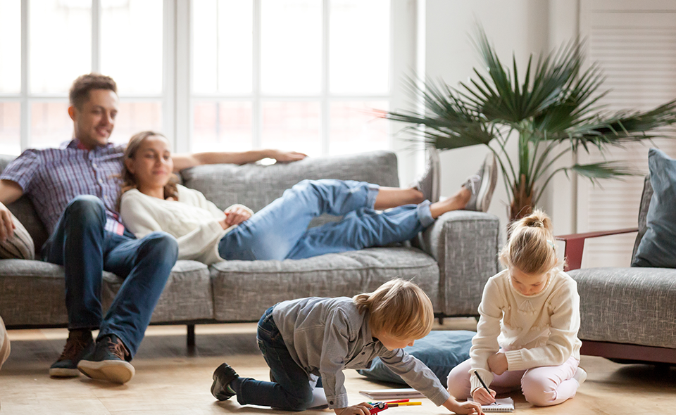 Couple sitting on the couch watching their kids play on the floor