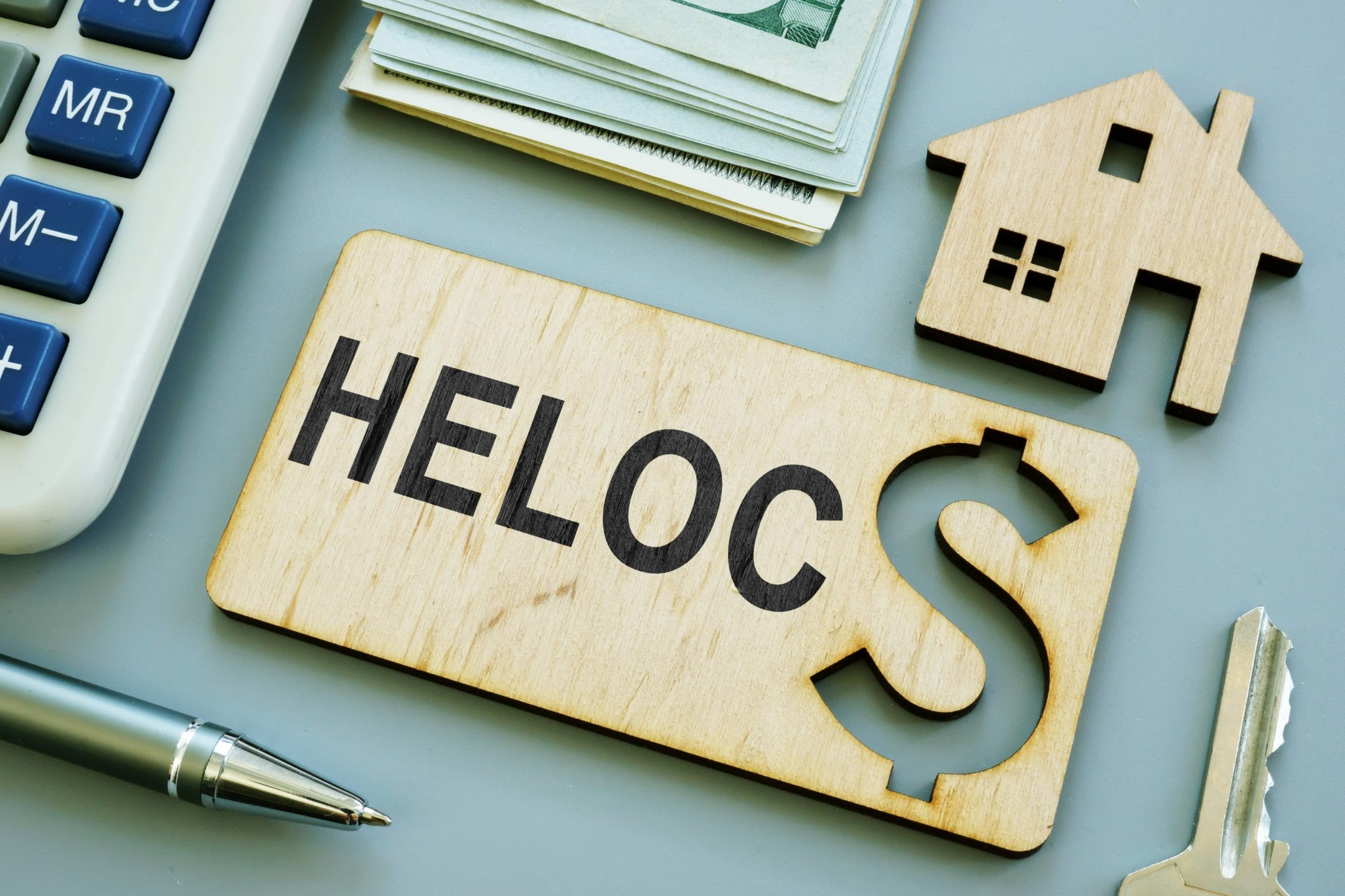 Wooden heloc sign with a dollar sign carved into laid out on a table with a wooden house and calculator.