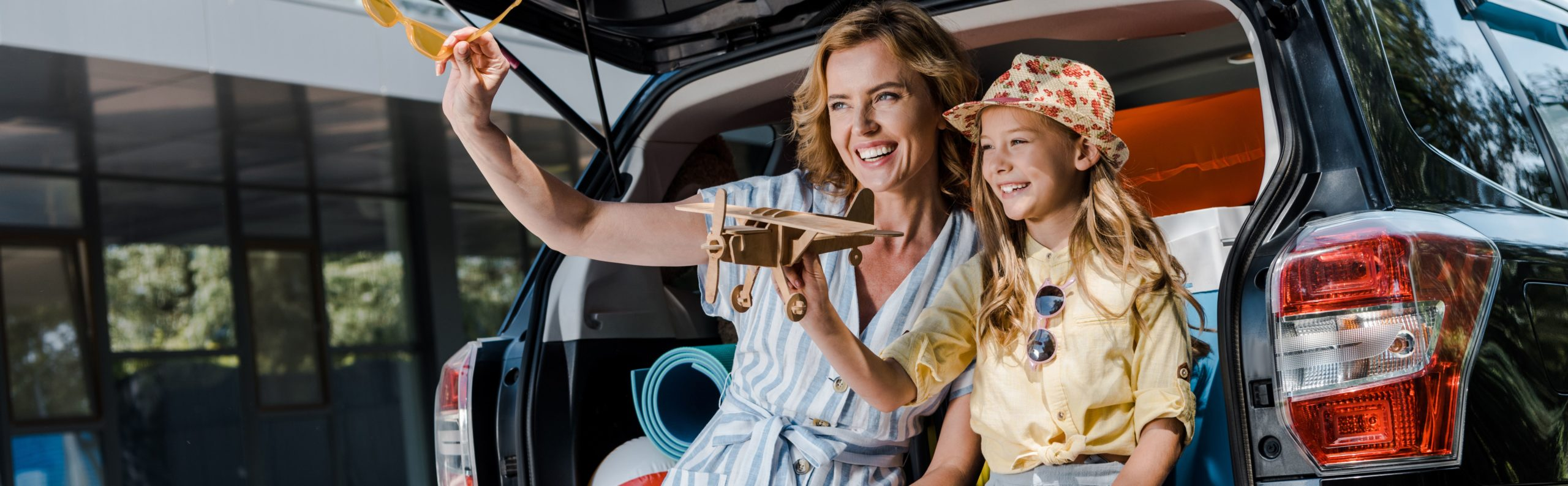 Mother and daughter sitting in the trunk of vehicle playing with a toy plane.