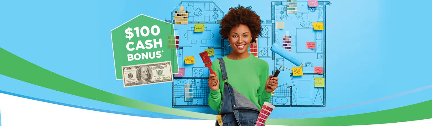 Woman in a green sweater and overalls holding a paint brush and a paint roller as she stands over a blueprint.