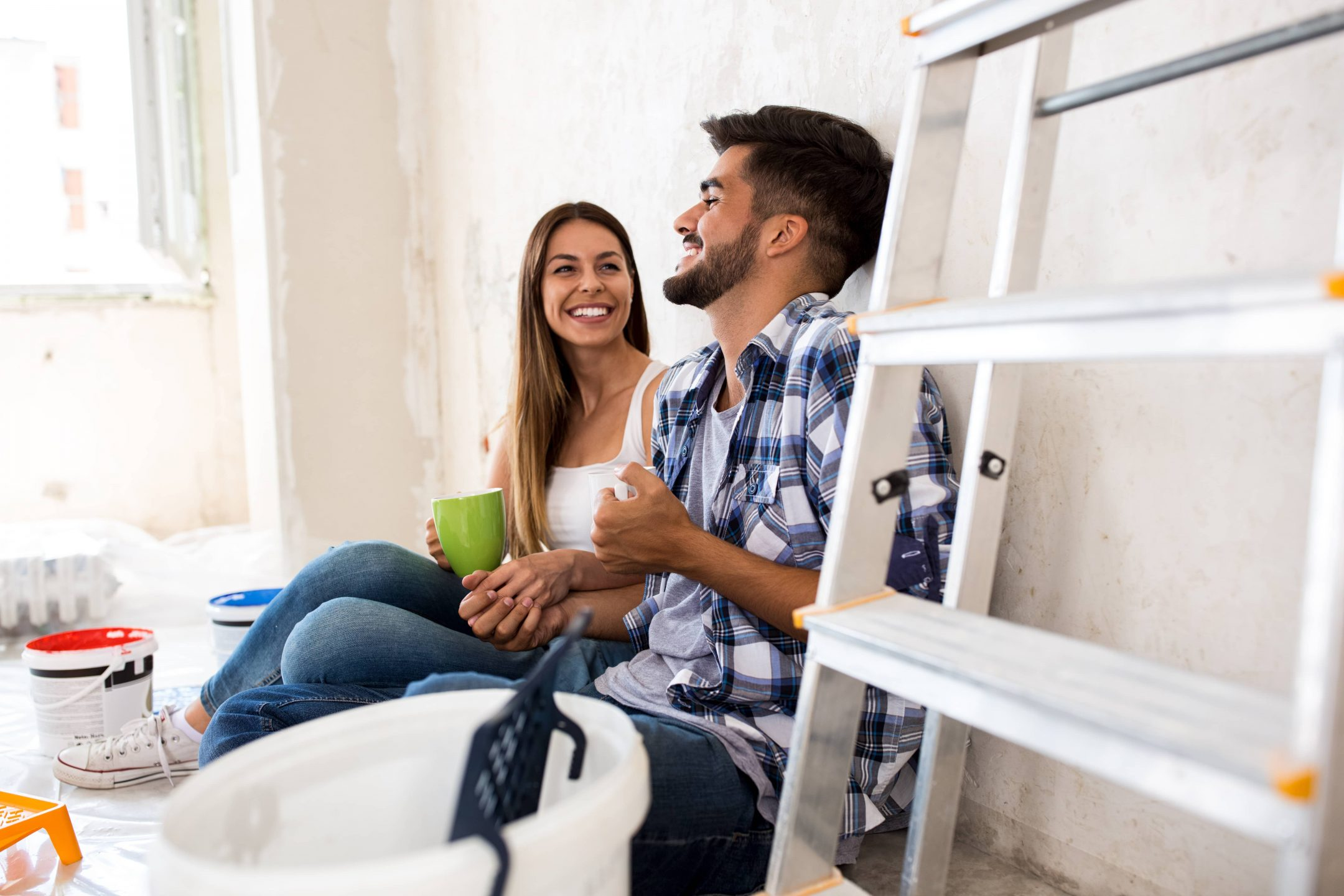 Young couple sitting on the floor taking a break from the home improvement project they have been working on.